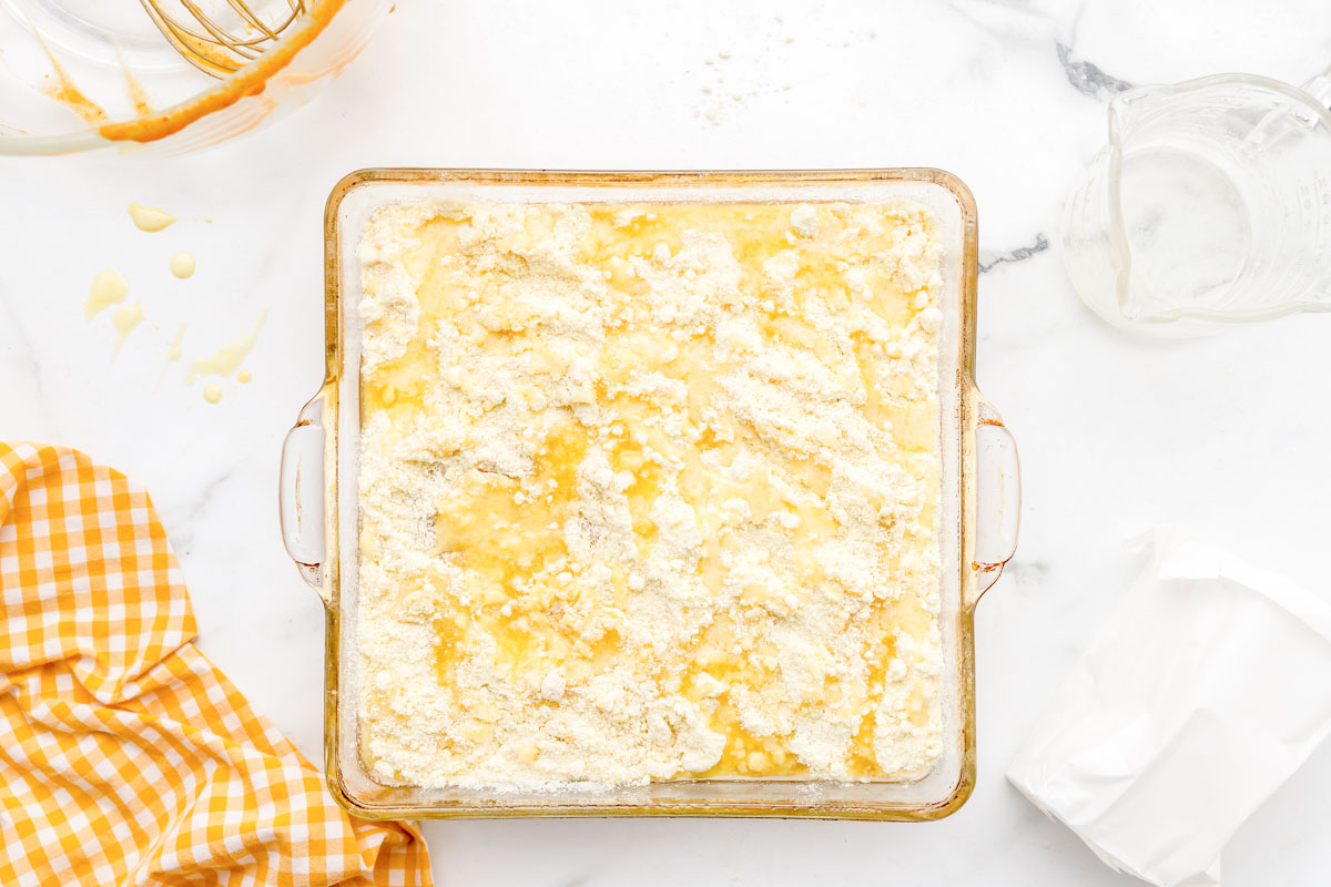 Butter and cake batter topped cobbler in a glass baking dish