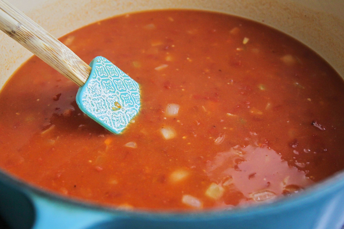 Tomato bisque soup cooking in a blue dutch oven
