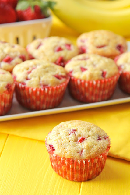 A strawberry banana muffin in front of a plate full of muffins