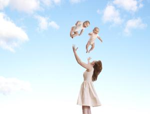 Woman throwing babies in air (digital composite)