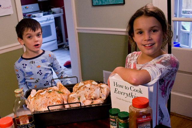 Two kids in the kitchen helping.