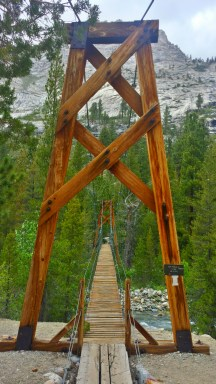 """A Suspension Bridge makes its way over a river gorge. The sign says, """"One at a time only."""""""