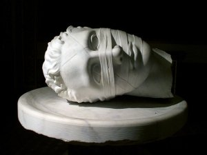 Sculptor of head covered in bandages