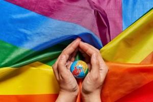 Hands holding globe on the rainbow flag