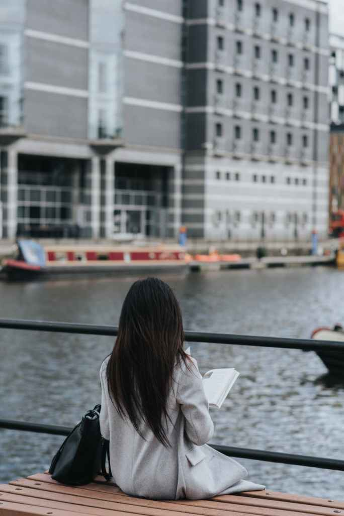 young woman enjoying pastime with book on embankment