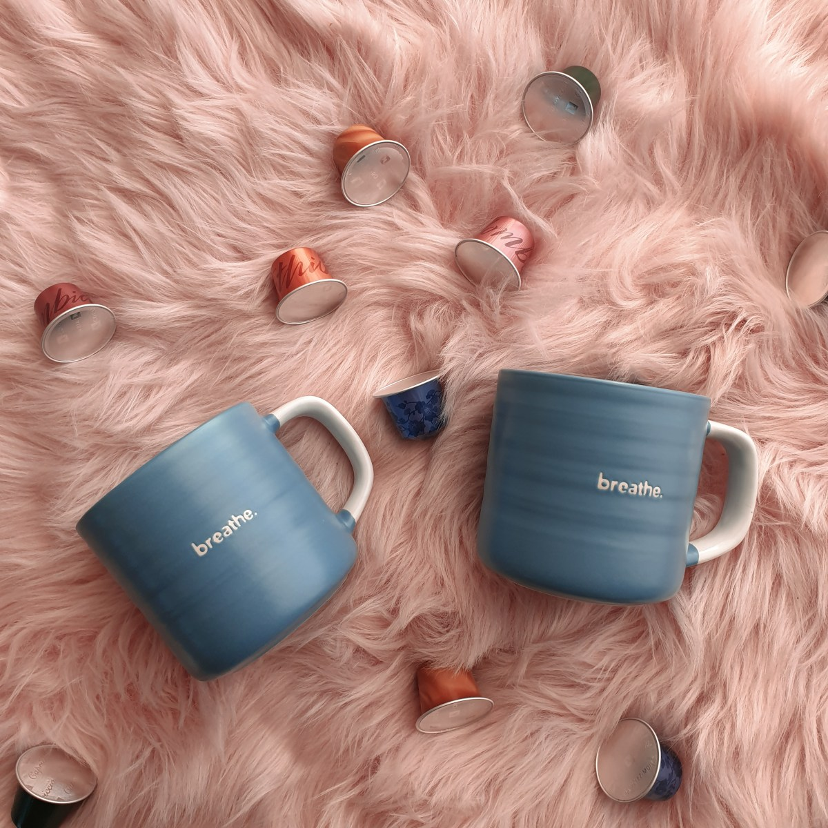 Woolworths mugs, pink rug with mugs and Nespresso pods
