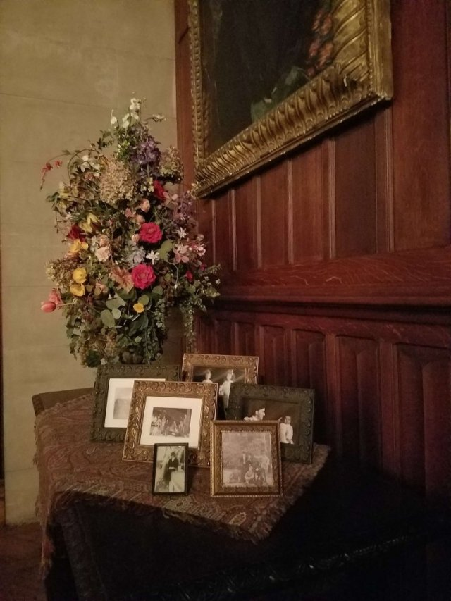 Family photos displayed on a table in the Tapestry Room of the Biltmore House personalize the space.