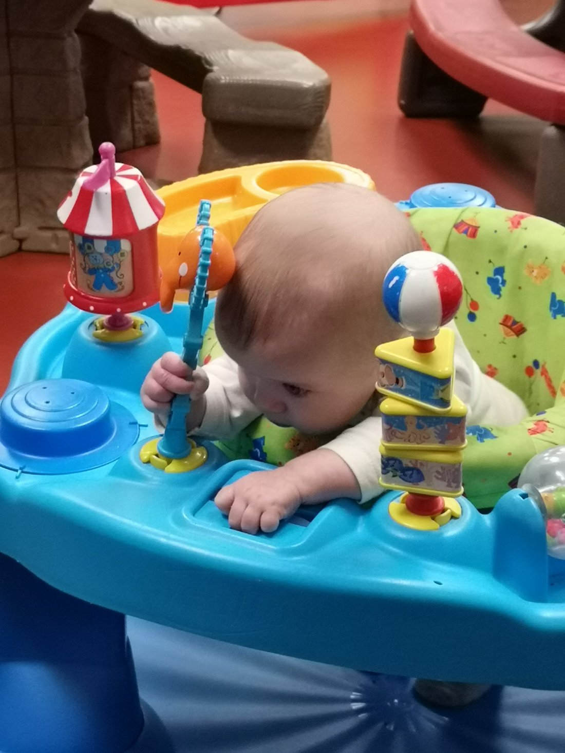 Baby in play toy trying to eat toys.