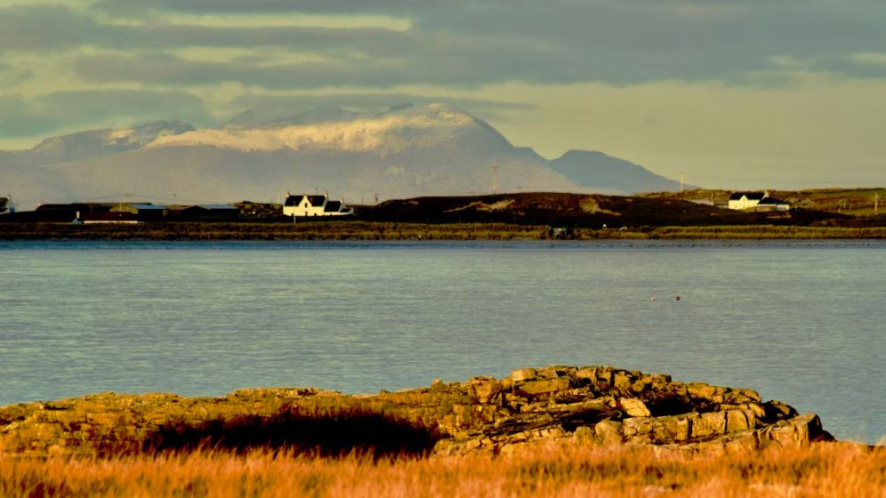 The Isle of Rum viewed across Gott Bay as the sun sets