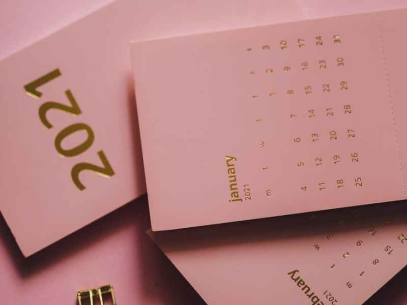 modern calendars near metal clips on pink background
