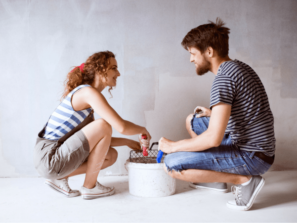 Man and woman painting a wall together