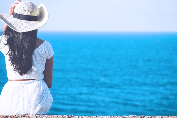 Woman sitting on the beach enjoying a vacation