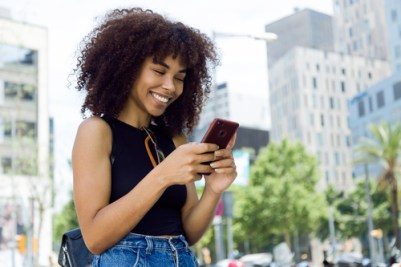 Women following Ibotta on social media with her phone