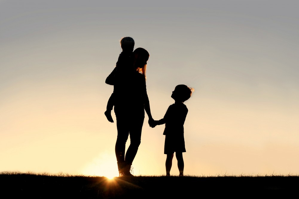 Silhouette of a young mother lovingly holding hands with her happy little child while holding his baby brother outside in front of a sunset in the sky.