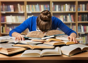 Student who has fallen asleep with her head on a book while studying