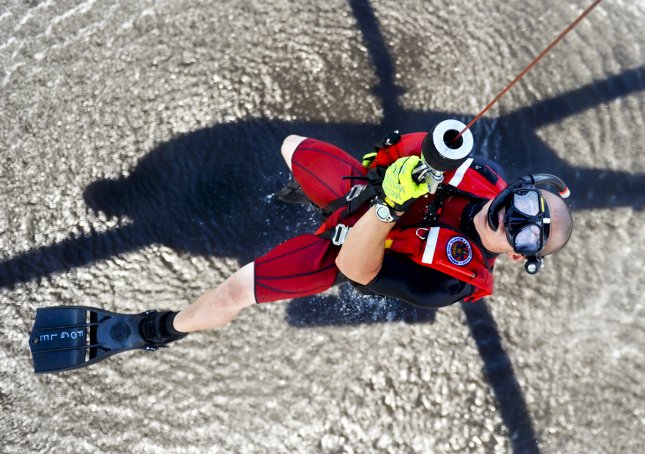 rescue swimmer brett fogle hangs from a helicopter hoist cable over the river in Elizabeth City North Carolina