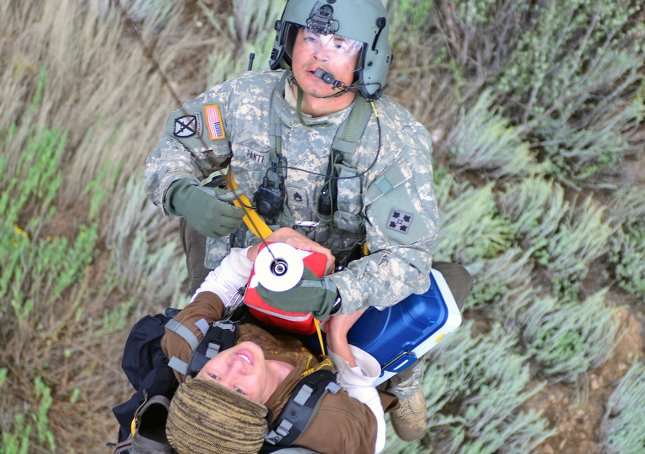 rescuer riding up to a helicopter on a lifesaving systems rescue seat