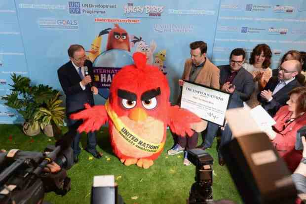 "NEW YORK, NY - MARCH 18: (L-R) Mr. Ban Ki-Moon, 'Red', Jason Sudeikis, Josh Gad, Maya Rudolph, John Cohen and Cristina Gallach attend the United Nations Ceremony, Presentation and Photo Call naming Red, from the ""ANGRY BIRDS movie, Honorary Ambassador for the International Day of Happiness, to be observed around the world on March 20th, at United Nations on March 18, 2016 in New York City."
