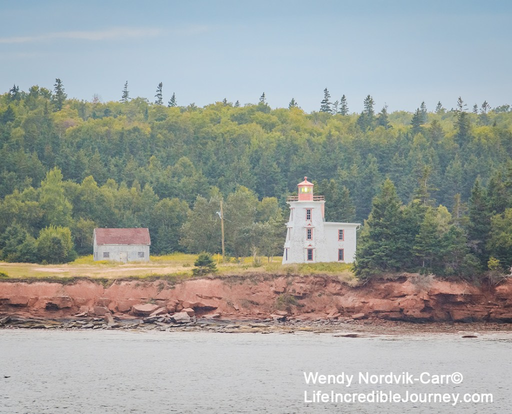 View of PEI historic Blockhouse Point Lighthouse and Amherst National Historic Site as as you leave port of call Charlottetown on a Holland America Cruise ship. The Blockhouse Point Lighthouse was built in 1887. This area is also famous for the impressive red sandstone cliffs and red sand beaches. Irish Moss can be found here as well.
