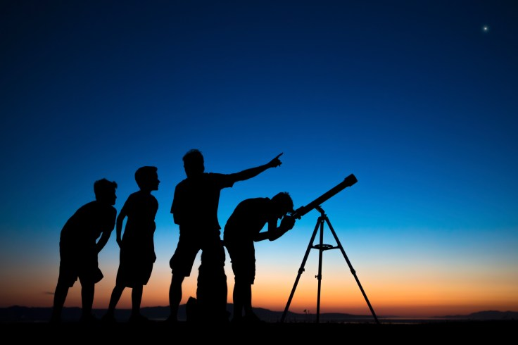 Dad and three sons on a clear night looking thru a telescope