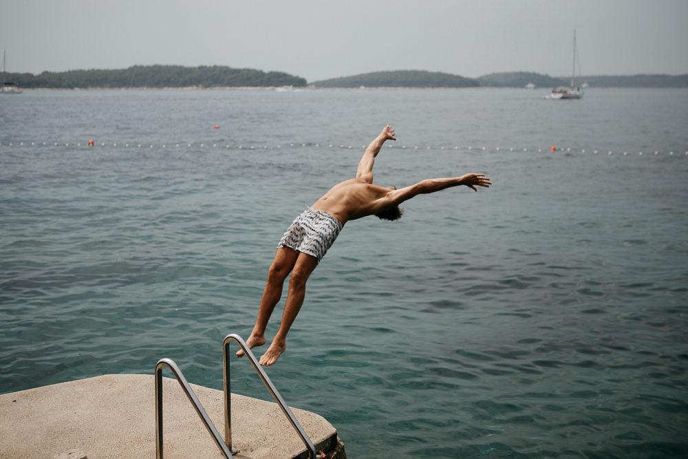 groomsmen diving backflip in Hvar Croatia on the wedding day