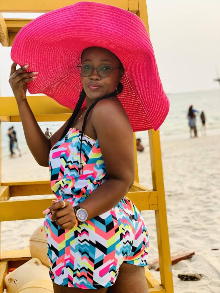lady in a pink hat and romper at the beach