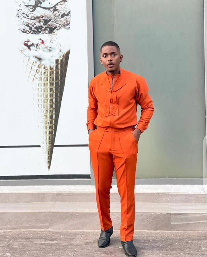 man wearing orange outfit with black shoes