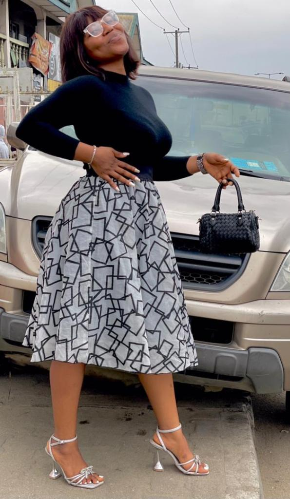 lady wearing black polo neck with midi skirt