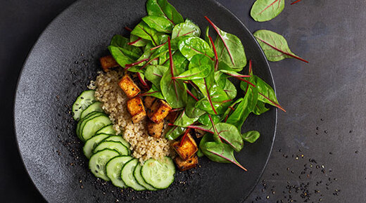 Vegan tofu poke bowl with baby chard and quinoa in a black dish on a black counter