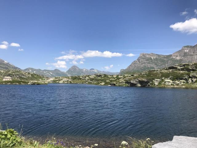 Alpine Lake directly at the San Bernardino Pass with Mountains in the back and blue Sky