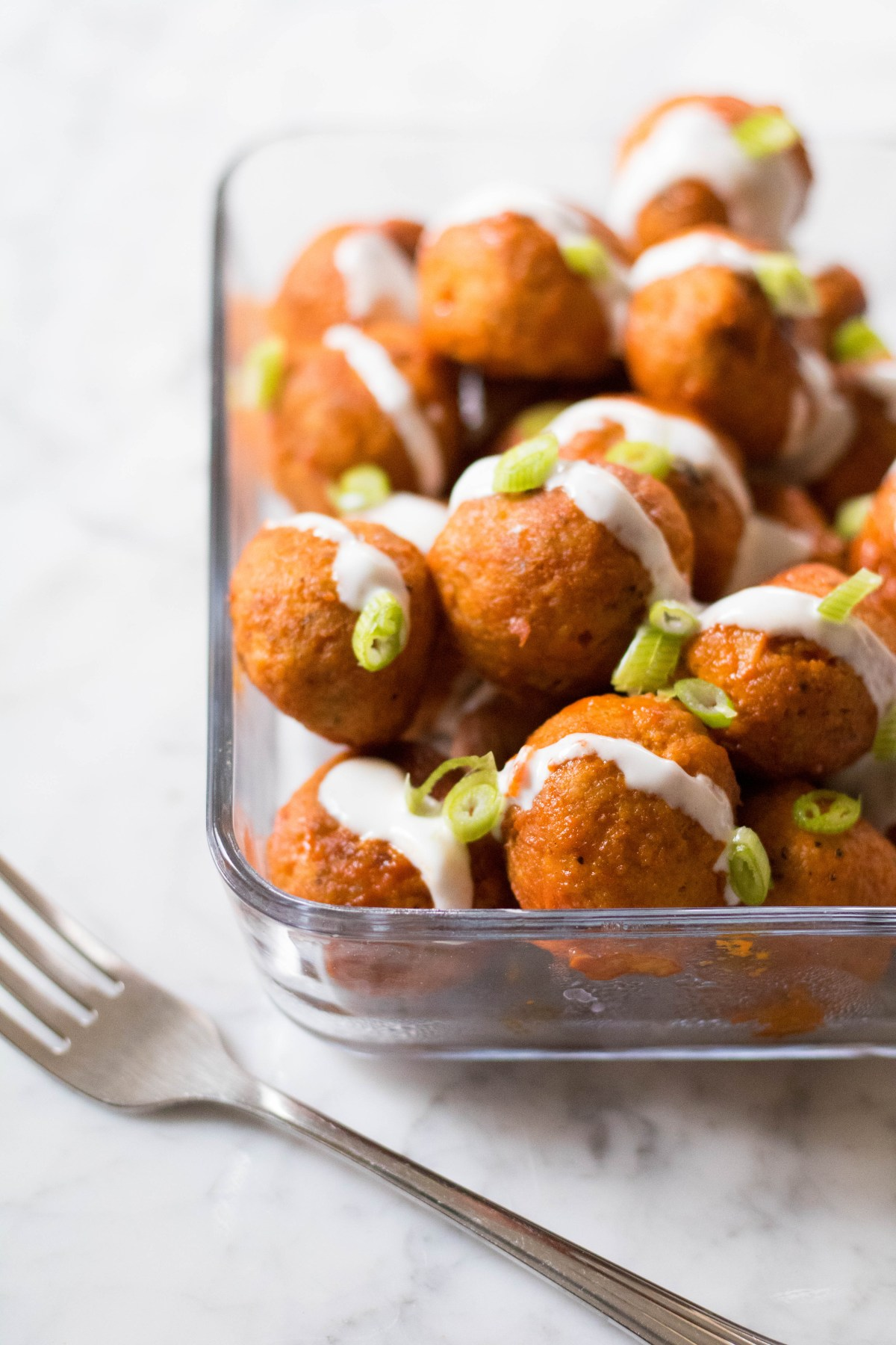 Container of healthy baked buffalo chicken meatballs.