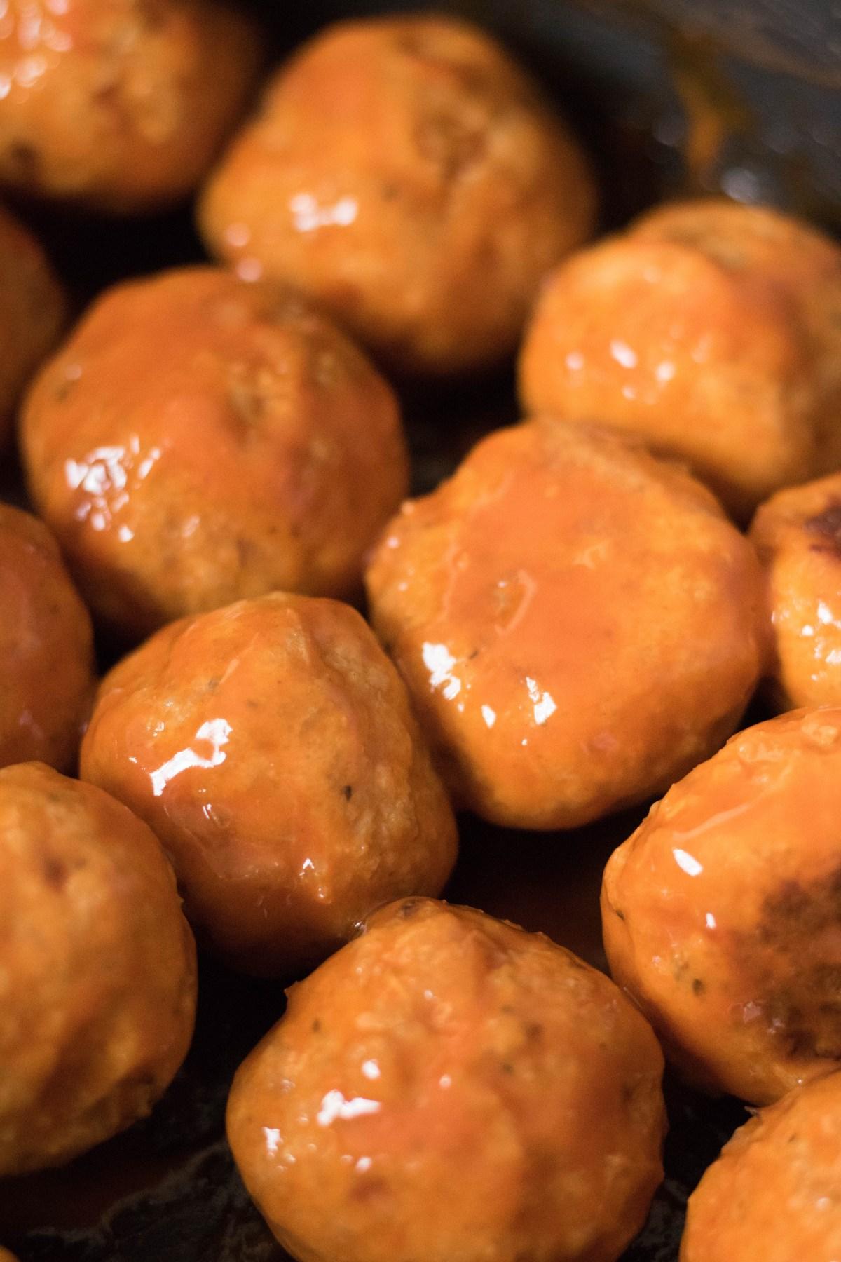 baked chicken meatballs coated in buffalo sauce