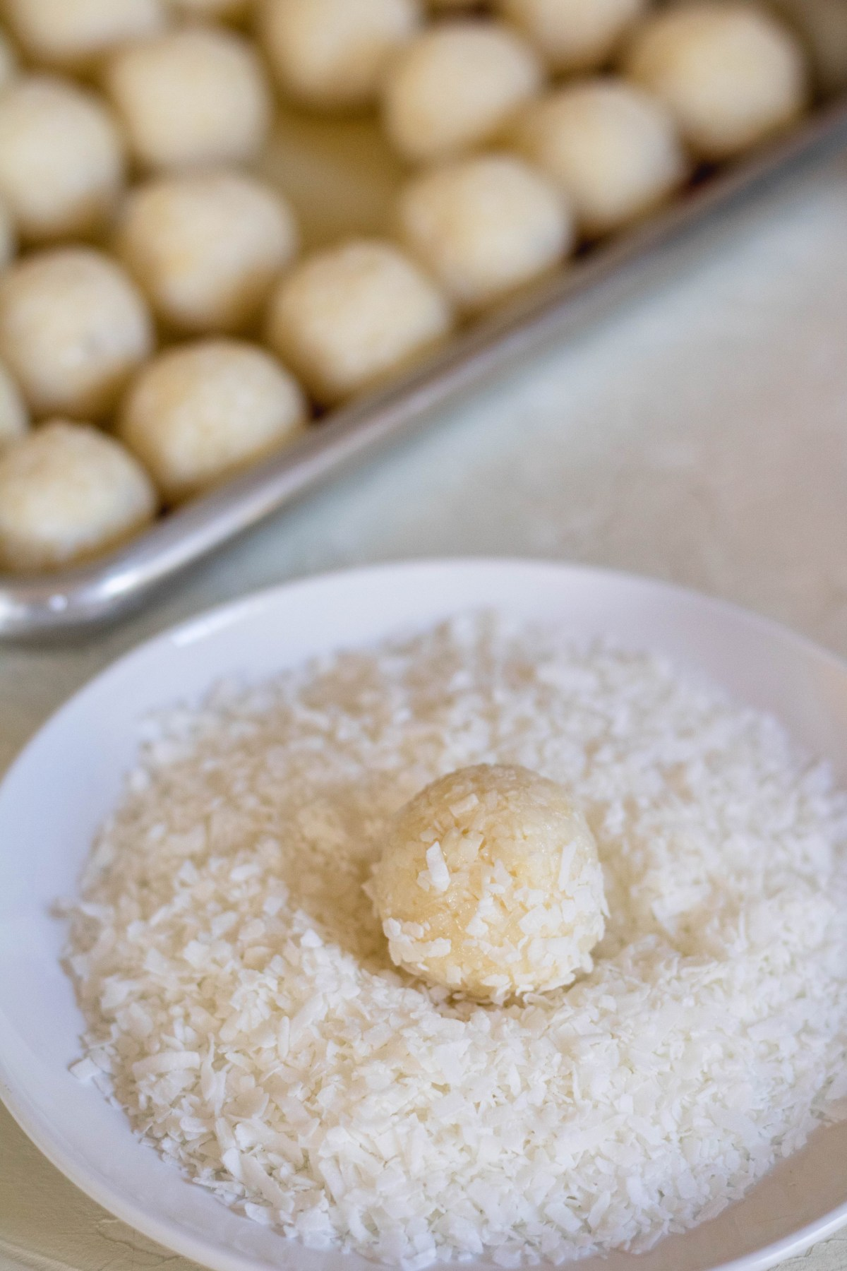 2 ingredient coconut balls coating in coconut