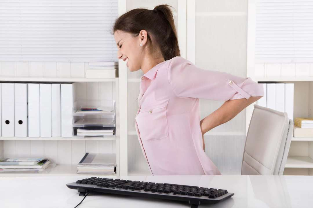 Young woman in an office suffering from back pain