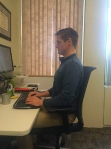 Example of how to sit properly in a desk. Notice how the posture keeps the spine upright.