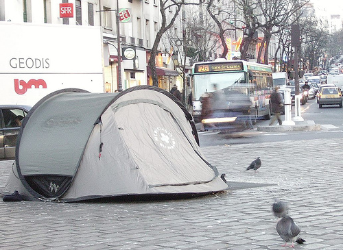 A tent on a busy street used by people without a home