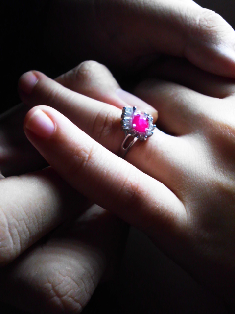 A boyfriend placing a light rose colored Amethyst on his girlfriend's ring finger at a proposal.