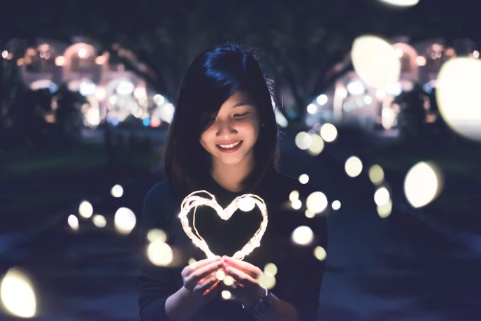 A girl holding a heart shape light