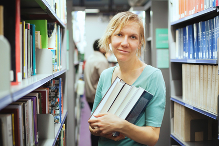 a college student holding many books in the library