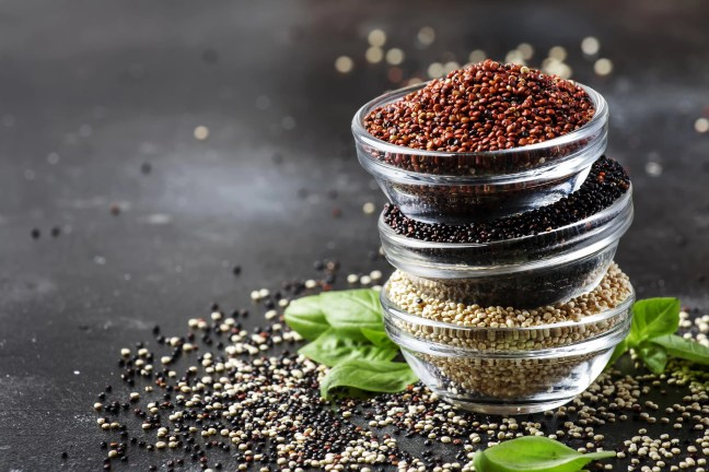 Black, white and red quinoa in bowls, raw quinoa groats assorted