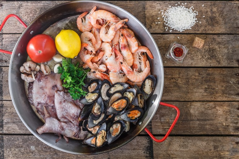 Raw seafood products in paella pan on a wooden table, top view