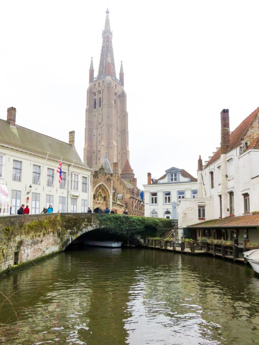 view of a church and canal in bruges