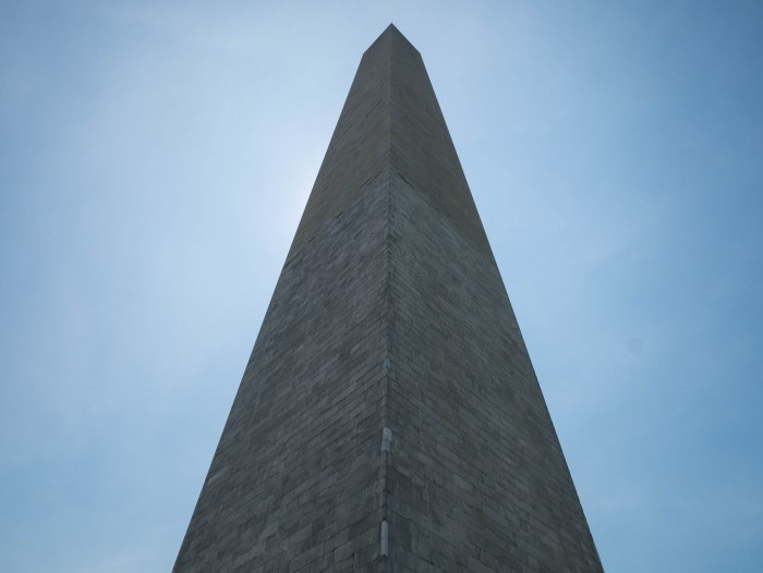 image looking up at washington monument dc with sun behind monument