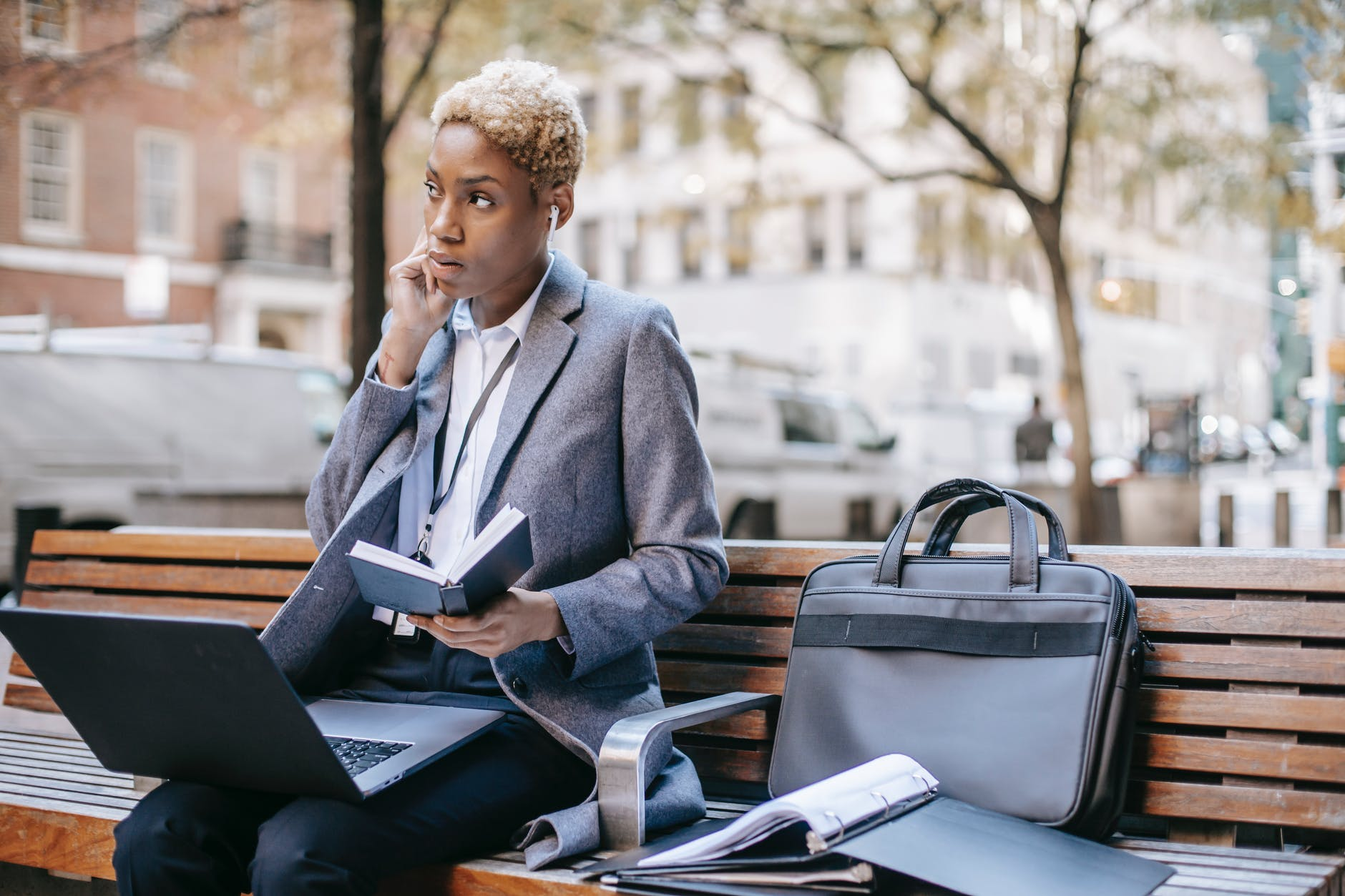 focused black businesswoman working on laptop on bench in park