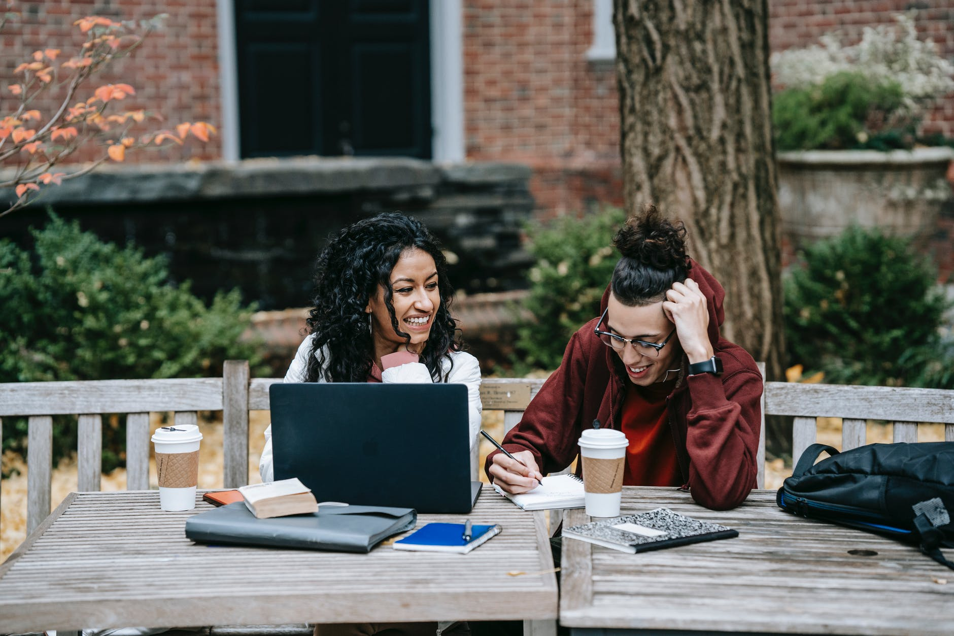 diverse students working together at table with laptop in park