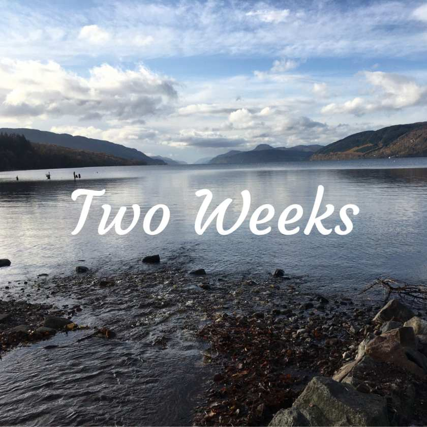 "A view of Loch Ness from Dores beach, looking out from the shore to the water. The words ""Two Weeks"" are written in white writing in the centre of the image"