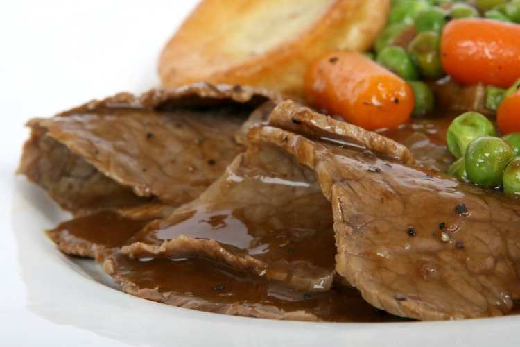 Roast beef dinner covered in gravy, with Yorkshire pudding, peas and carrots, all on a white plate - Sunday Lunch out for Dad's birthday January 2020