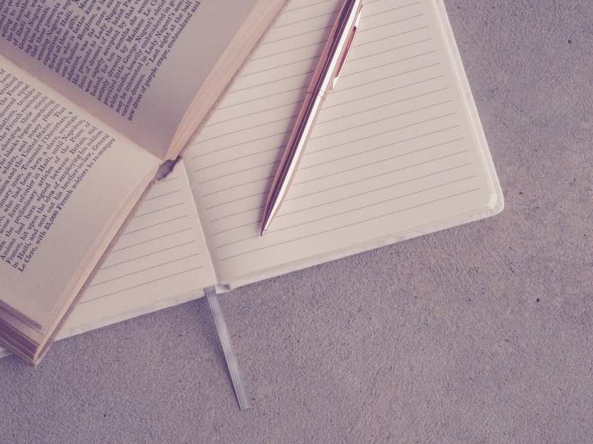 Background - A lined notebook left open on a blank page, overlayed with a novel open on a page that you cannot see the writing, and in the foreground is a rose gold pen