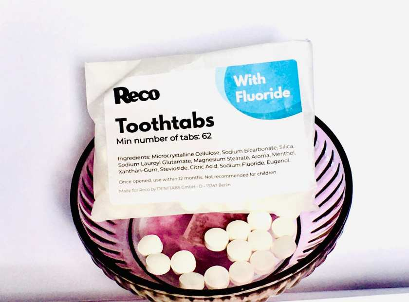 Reco's ToothTabs on display both in a purple dish and in their biodegradeable packaging against a white background