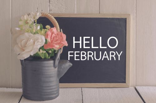 Chalkboard with Hello February written on it for February 2021 post with flowers in a watering can.